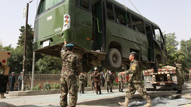 Soldiers prepare to remove a destroyed military bus at the site of the suicide attack in Kabul (AP)