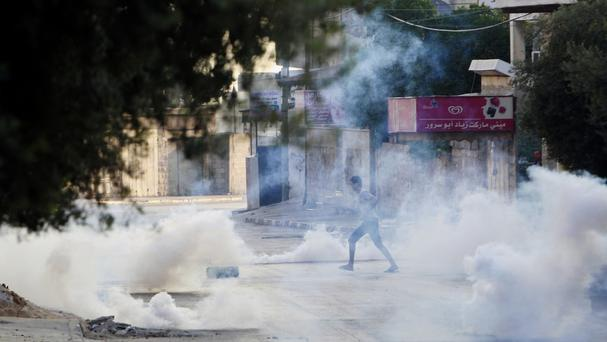 A Palestinian takes cover from tear gas fired by Israeli troops during clashes in the West Bank (AP)