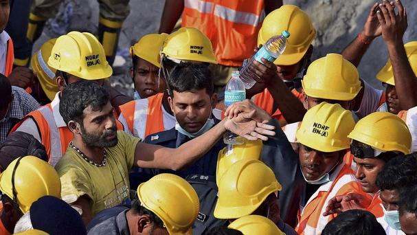 Rescuers stand around a man they found beneath the debris of a building that collapsed in India (AP)