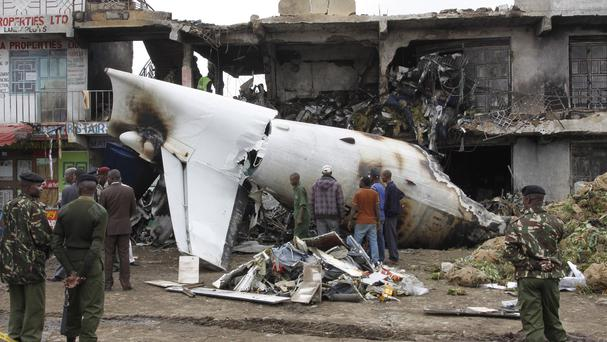 Soldiers look at the wreckage of the cargo plane after it crashed shortly after take-off in Kenya (AP)