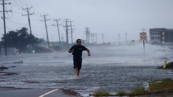 A man crosses a flooded road caused by Hurricane Arthur (AP Photo/Gerry Broome)