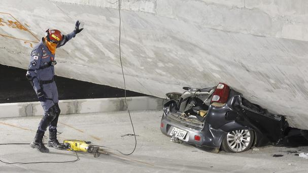 A car lies crushed underneath a collapsed bridge in Belo Horizonte, Brazil (AP/Victor R Caivano)