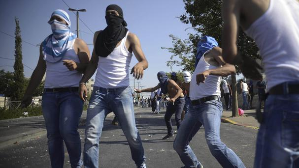 Palestinians throw rocks as they clash with Israeli security forces during the funeral of 16-year-old Mohammed Abu Khdeir in Jerusalem on Frida
