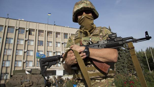 A Ukrainian government army soldier stands in front of the government building with a Ukrainian flag on the roof in the city of Slovyansk (AP)