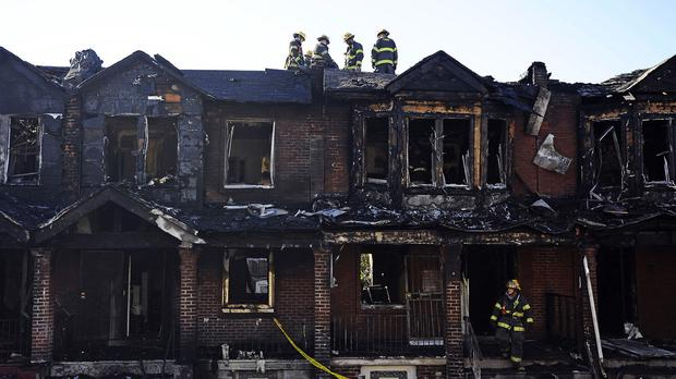 Philadelphia firefighters work on burned homes after a fire killed four children (AP)