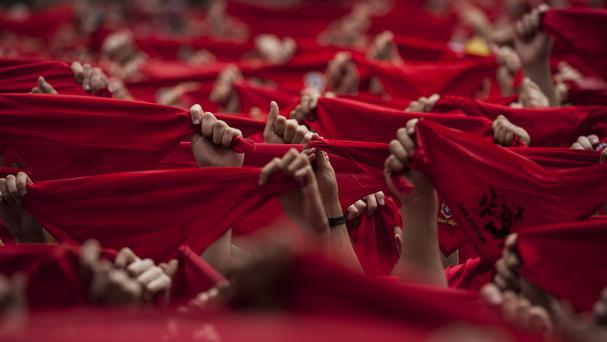 Revelers hold up their traditional red kerchiefs during the launch of the 'Chupinazo' rocket, to celebrate the official opening of the 2014 San Fermin fiestas, in Pamplona, Spain (AP)