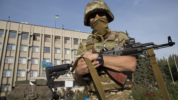 A Ukrainian soldier stands in front of the government building with a Ukrainian flag on the roof in the city of Slovyansk (AP)