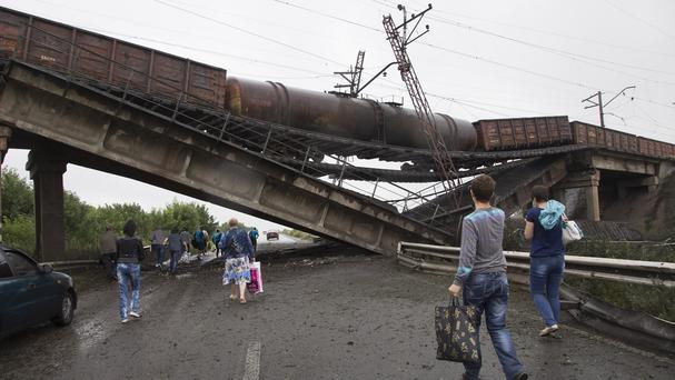People walk under a destroyed rail bridge over a main road leading into the east Ukraine city of Donetsk (AP)