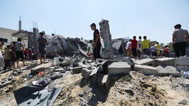 Palestinians inspect the rubble of a house after it was hit by an Israeli missile strike in Khan Younis, southern Gaza Strip (AP)