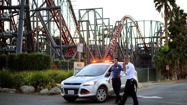 Six Flags Magic Mountain amusement park security staff in California beside the Ninja rollercoaster which hit a tree branch leaving about 20 people hanging 30 feet in the air (AP/Los Angeles Daily News)