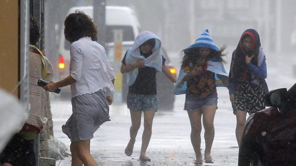 Women walk through strong winds and rain in Naha, Okinawa, as Typhoon Neoguri pounded across the southern Japanese islands of Okinawa (AP/Kyodo News Agency)