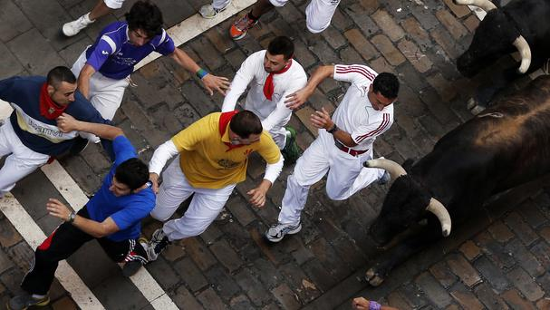 Revellers are chased by fighting bulls during the San Fermin festival in Pamplona, Spain (AP)