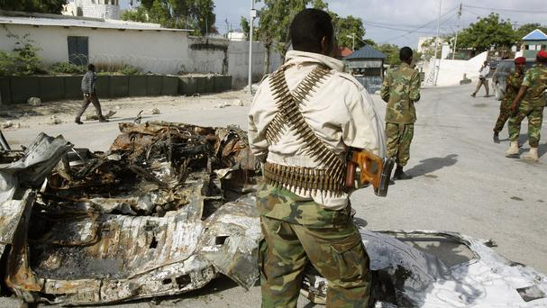 Somali soldiers stand near the wreckage of a car bomb that was detonated at the main gate of the presidential palace in Mogadishu (AP)
