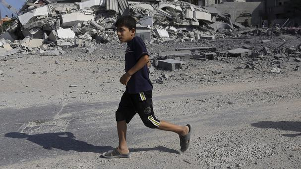 A Palestinian boy passes the rubble of a house after it was hit by an Israeli missile in the Nuseirat Refugee Camp, central Gaza Strip (AP)