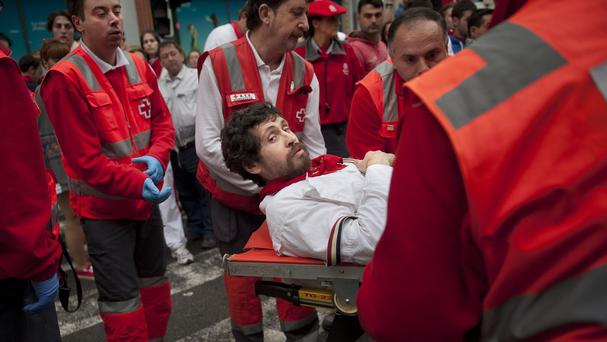 US runner Bill Hillmann is carried on a stretcher after being gored on his right leg by a fighting bull during the San Fermin festival in Pamplona, Spain (AP)