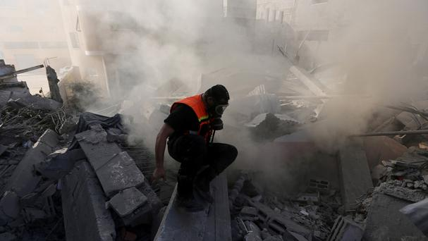 A Palestinian inspects the rubble of a house after it was hit by an Israeli missile strike in Gaza City (AP)