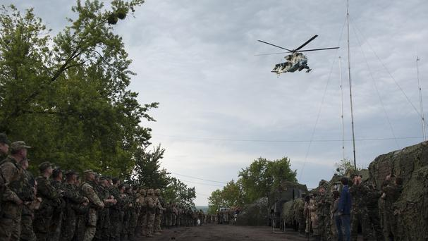 A Ukrainian Army helicopter flies over a military base while troops wait for Ukrainian President Petro Poroshenko in Devhenke (AP)