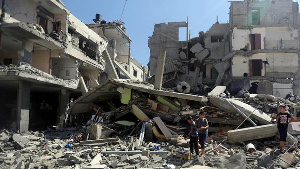 Palestinians inspect the rubble of a building after it was hit by an Israeli missile strike in Gaza City (AP)