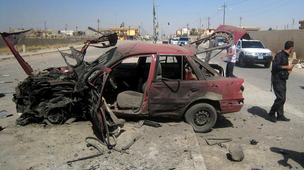 The aftermath of a bomb attack on cars lined up at a fuel station in Kirkuk (AP)