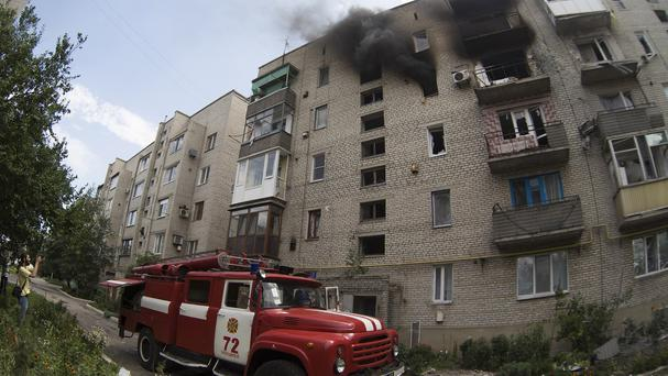 A fire truck arrives at a burning building after shelling near the city of Donetsk (AP/Dmitry Lovetsky)