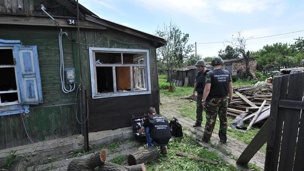 Officials examine a house in the Russian town of Donetsk, where a Ukrainian shell is alleged to have killed one person and seriously injured two others (AP Photo/Sergei Pivovarov)