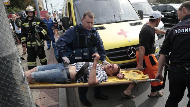 Paramedics and a police officer carry an injured man from a subway station after a rush-hour subway train derailment in Moscow (AP)