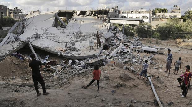 Palestinians inspect the rubble of a destroyed building after it was hit by an Israeli air strike in Beit Lahiya, in the northern Gaza Strip (AP)