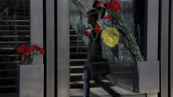 Flowers are fixed on doors as a commuter walks past an entrance of Slavaynsky boulevard subway station in Moscow (AP)