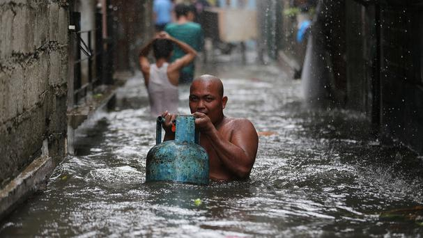 A man negotiates a flooded area as Typhoon Rammasun nears suburban Quezon city in the Philippines (AP/Aaron Favila)