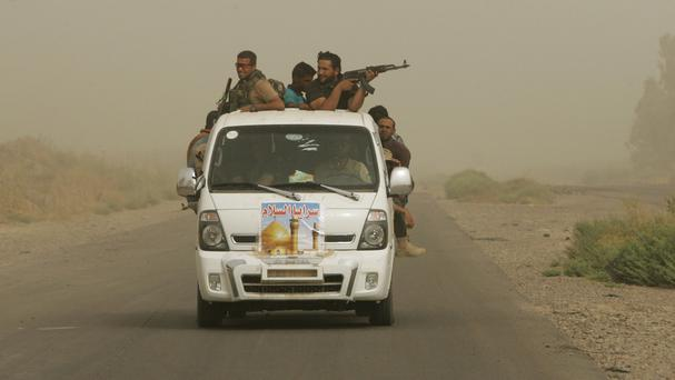 Iraqi fighters on patrol during a sand storm in Samarra (AP)