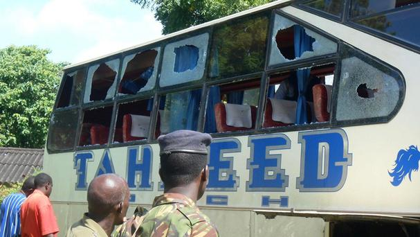 A Kenyan police officer with civilians watches the Taheed Bus at Lamu police station (AP)