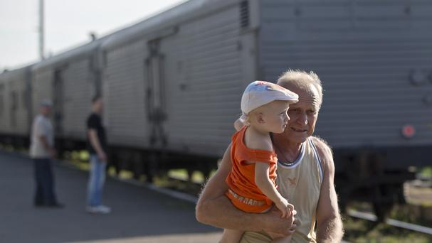A man holds a baby as he walks next to a refrigerated train loaded with the bodies of jet crash victims in Torez, eastern Ukraine (AP)