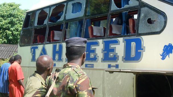 A police officer and civilians watch a bus in Lamu, Kenya, where seven people were killed in a gun attack (AP Photo)