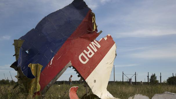 A man walks past a piece of the crashed Malaysia Airlines plane near the village of Hrabove, eastern Ukraine (AP)