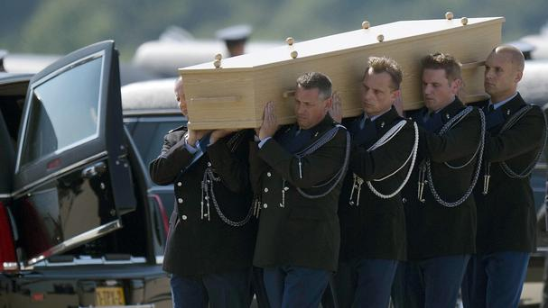 Dutch soldiers carry coffins with the first bodies of passengers and crew killed in the crash (AP Photo/Martin Meissner)