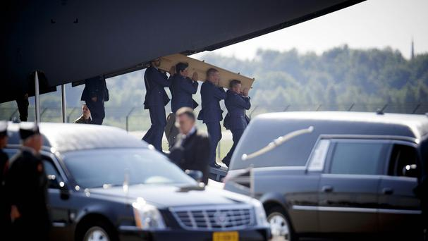 Pallbearers carry a coffin out of a military transport plane as the first bodies of those killed in the Malaysia Airlines crash in Ukraine arrive in the Netherlands (AP)