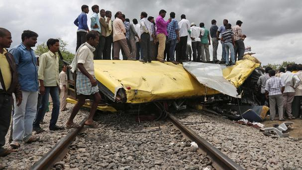 Indians stand on top of a bus that was crushed when a train crashed into it in Medak district in the southern Indian state of Telangana (AP)