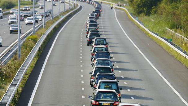 A convoy of hearses bearing the remains of passengers and crew killed on Malaysia Airlines Flight 17 makes its way along a road near Boxtel, Netherlands (AP)