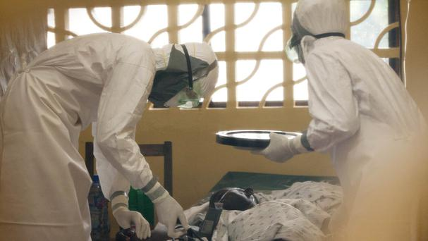 Dr Kent Brantly, left, treats an Ebola patient at the Samaritan's Purse Ebola Case Management Centre in Monrovia (AP Photo/Samaritan's Purse)