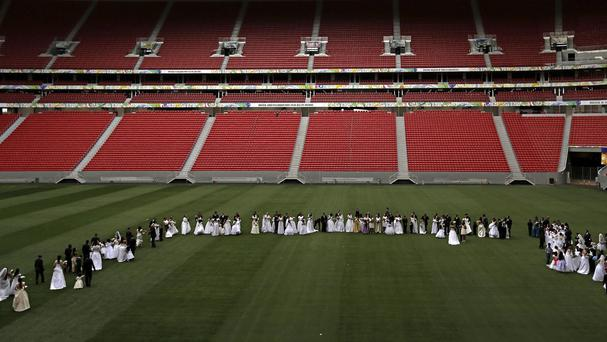 Couples gather on the pitch at the Estadio Nacional for a collective civil marriage ceremony (AP)