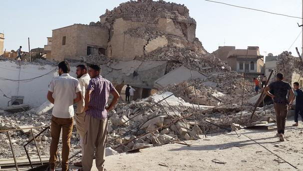 People inspect the destroyed Mosque of the Prophet Jirjis in central Mosul, Iraq (AP)