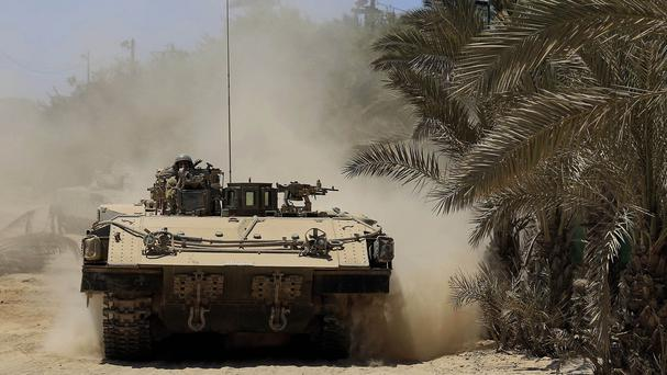An Israeli armoured vehicle stirs up dust near the Israel-Gaza border (AP)