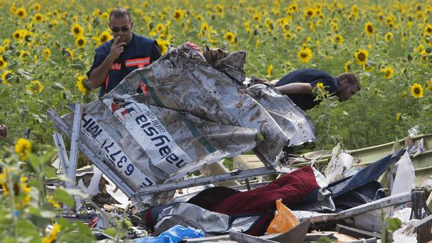 Dutch investigators examine pieces of the crashed Malaysia Airlines Flight 17 (AP)