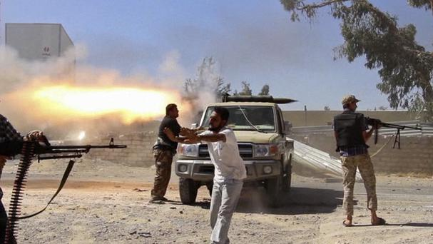 Fighters from the Islamist Misarata brigade fire towards Tripoli airport. (AP Photo/AP video)