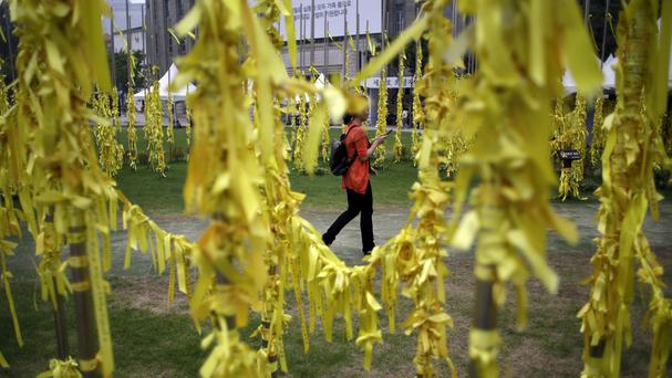 A woman walks near yellow ribbons with messages for missing passengers and victims aboard the sunken South Korean ferry Sewol (AP)