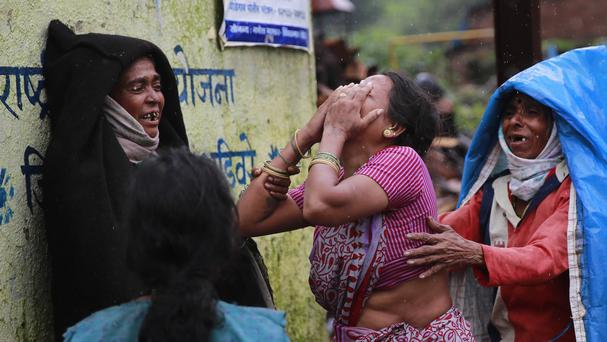 Relatives wail after seeing the body of a victim in the massive landslide in Malin village in India. (AP Photo/Rafiq Maqbool)