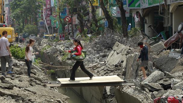 A woman crosses over a trench caused by a massive gas explosion in Kaohsiung, Taiwan (AP)
