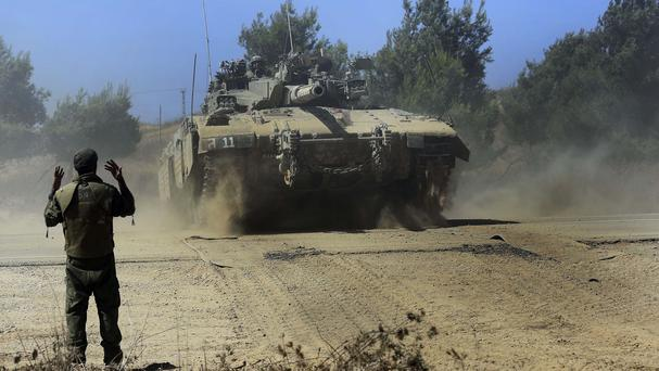 Israeli reservists direct a Merkava tank across a road as it advances towards the Israel Gaza border (AP)