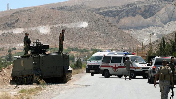 Lebanese army soldiers stand guard as ambulances wait at the entrance of Arsal, a Sunni Muslim town near the Syrian border, in eastern Lebanon (AP)