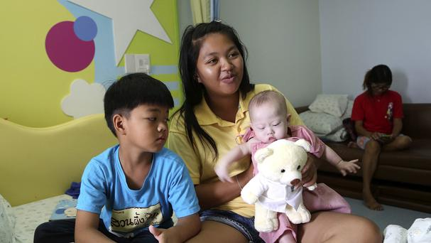 Pattaramon Chanbua, 21, poses with her children Game, 7, left, and baby boy Gammy at a hospital in Chonburi province, south-eastern Thailand (AP)